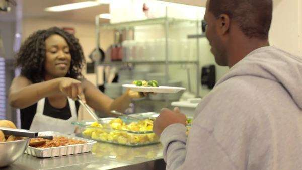 Volunteers in kitchen of homeless shelter serves food to people standing in line. Royalty-free stock video