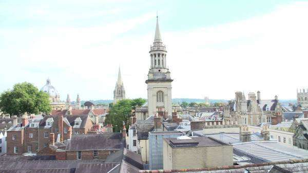 Camera pans across the Oxford city skyline showing buildings, churches and the dome of the Radcliffe Camera. Royalty-free stock video