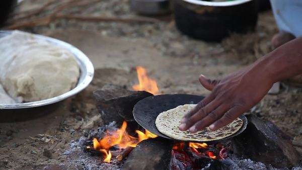 Close up shot of people making chapatis on camp fire Royalty-free stock video