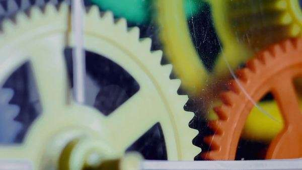Colorful plastic gears rotate synchronously  Old toy clock mechanism with  scratches on the glass  stock footage