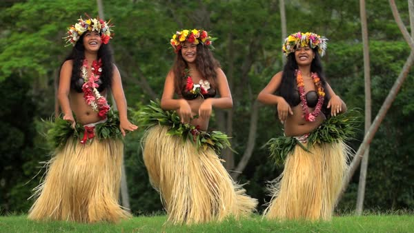 barefoot tahitian women in hula skirts and flower