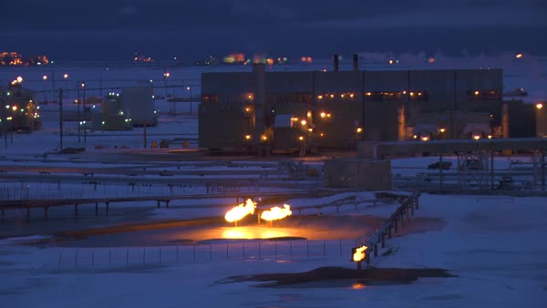 Aerial winter view of illuminated plant and natural gas flare stack Prudhoe  Bay oilfield production refinery and pumping station Arctic circle Alaska
