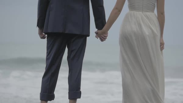 Hand-held shot of a bride and a groom holding hands on a beach Royalty-free stock video