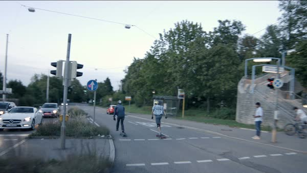 Two skateboarders cross a road and set off Royalty-free stock video