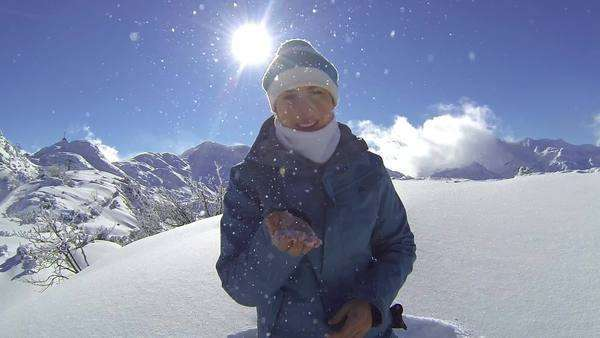 Young woman in nature blows snow into camera Royalty-free stock video