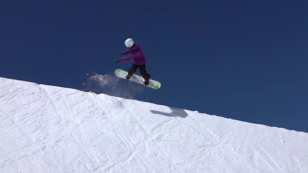 SLOW MOTION: Young pro snowboarder riding the half pipe in big mountain snow park, jumping high out of the halfpipe wall, performing tricks and rotations with grabs in sunny winter  Royalty-free stock video