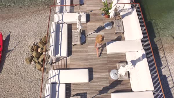 AERIAL: Cheerful young female in light summer dress walking and spinning between white daybeds, tables and loungers in empty luxury cocktail bar on wooden pier overlooking stunning turquoise ocean Royalty-free stock video