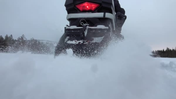 SLOW MOTION, CLOSE UP: Snowmobile takes off and sprays snow into the  camera  Sled riding race in backcountry  Snowmobile tracks spinning,  kicking up