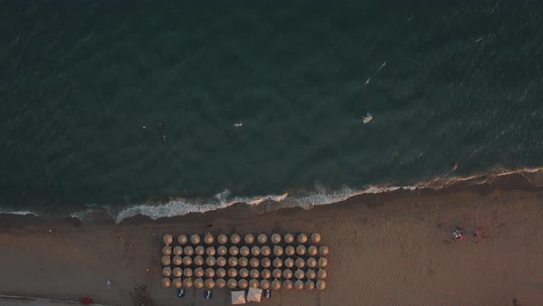 Distant Aerial View Of Sea And Shore With Rows Of Sunbeds Straw Umbrellas And Few People At The Beach Stock Footage