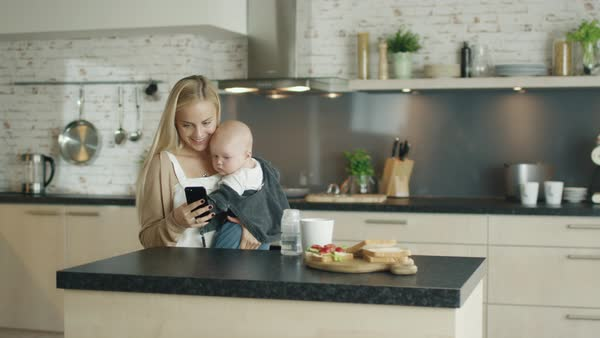 Young mother holds her beautiful child while being in the kitchen Royalty-free stock video