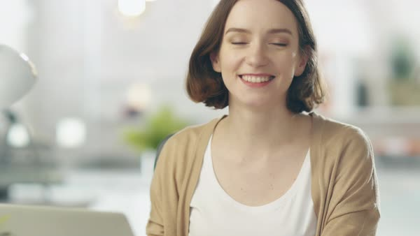 Focused young woman stops working on her laptop and smiles at the camera. her background is blurred. Royalty-free stock video