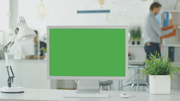 Close-up of a green screen on a personal computer. In background blurred and brightly lit office where people go through office routine. Royalty-free stock video