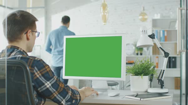 Close-up of a man sitting at his desk with green screen pc on the table. In background blurred and brightly lit office where people go through office routine. Royalty-free stock video