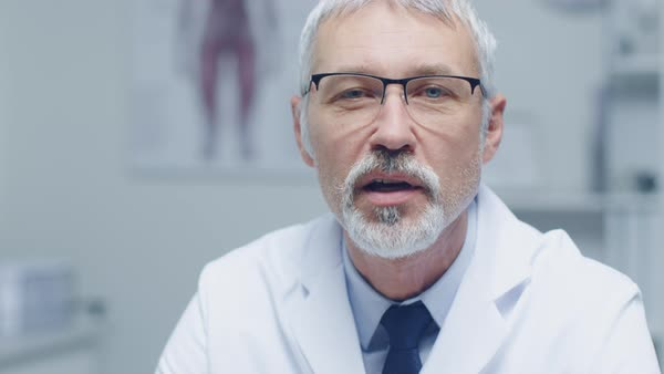 Close-up of a experienced gray haired senior medical practitioner talking into camera. Portrait shot in modern and light office. Royalty-free stock video