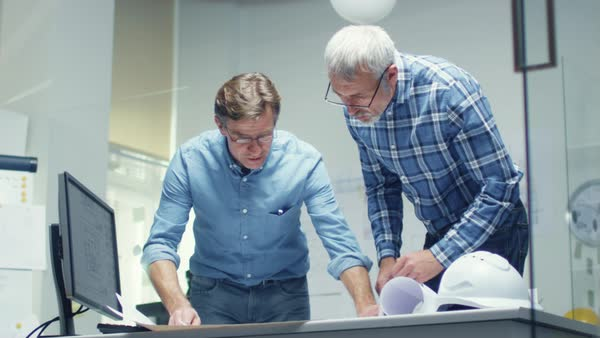 Two senior engineers work with schemes and blueprints while standing over working table. They have discussion on the subject of various technical matters concerning their project. Shot in slow motion. Royalty-free stock video