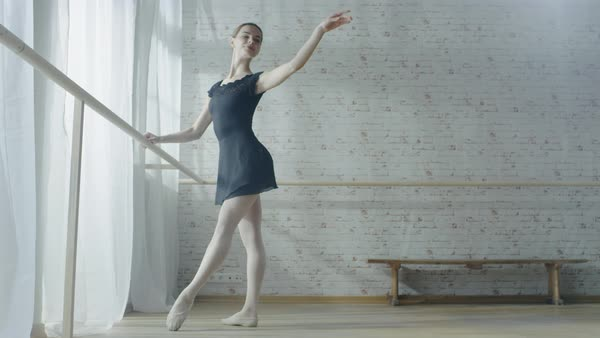 Long shot of a young and beautiful ballerina dancing at the barre Royalty-free stock video
