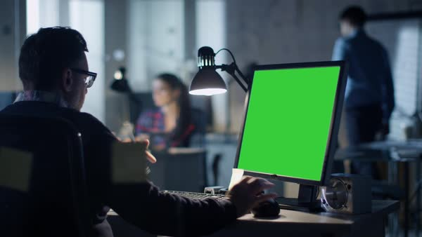 Late at night industrial engineer sits at his desk working on a computer with green screen on Royalty-free stock video
