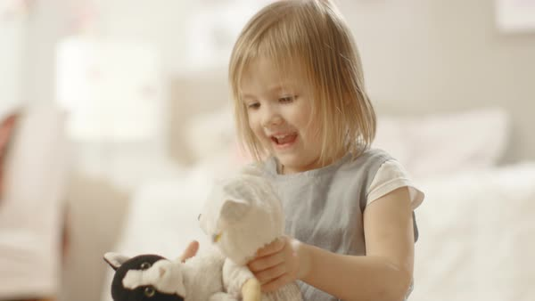Happy little girl plays with plush toys in her room. Royalty-free stock video