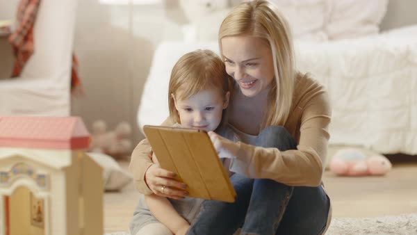 Beautiful mother and her little daughter have good time reading children's books on a tablet computer. Children's room is full of toys. Royalty-free stock video