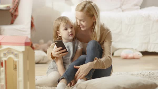 Beautiful mother and her little daughter have good time talking, mother holds smartphone. Children's room is full of toys. Royalty-free stock video