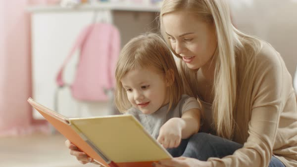 Beautiful young mother and her cute little daughter read children's book together. Children's room is pink and full of toys. Royalty-free stock video