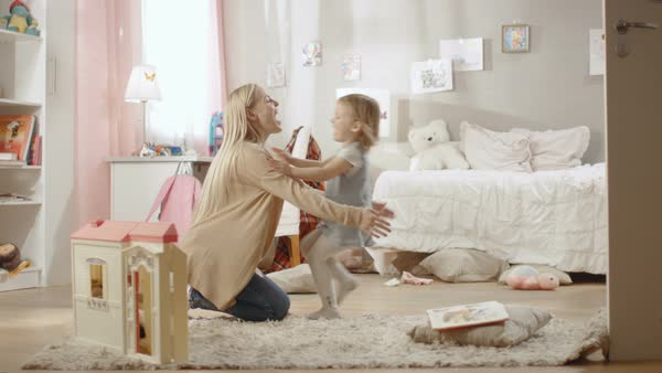 Cute blonde girl runs towards her young mother and they hug. Children's room is pink, has drawings on the wall and is full of toys. Slow motion. Royalty-free stock video