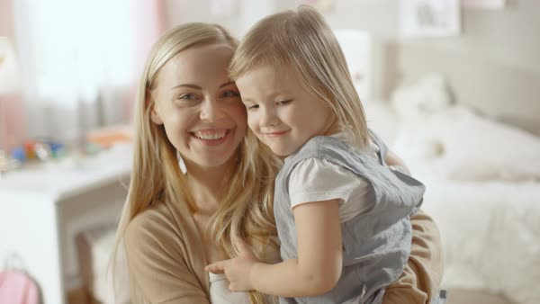 Young beautiful mother holds her little cute daughter in her arms. They both look and smile into the camera. Royalty-free stock video