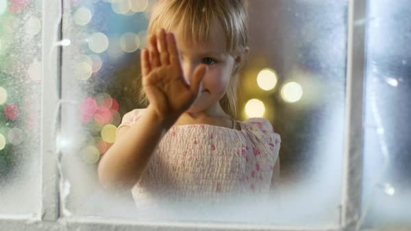 On Christmas Eve Cute Little Girl Looks Through the Snowy, Frozen Window and Smiles. Royalty-free stock video