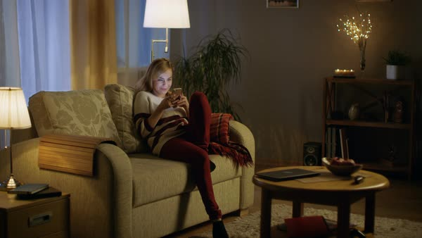 Beautiful Young Woman Enters Living Room In The Evening. Sits On Her Sofa  And Starts Using Smartphone.   Stock Video Footage   Dissolve