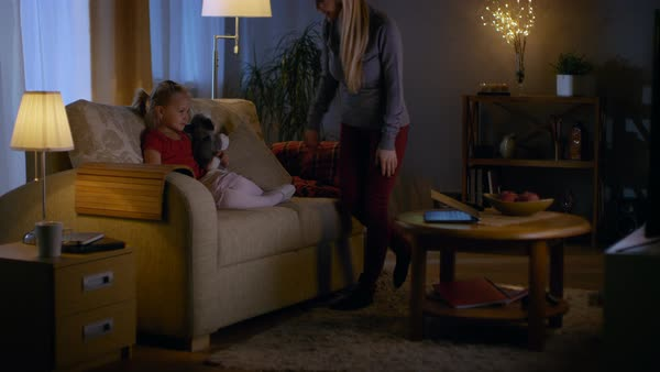In the evening little girl sits on a couch in a living room. She holds her soft toy and watches tv, her beautiful mother joins comes in and joins her of a sofa. Royalty-free stock video