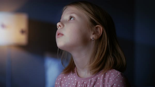Curious little girl in her bedroom at night, stands on tiptoe and looks out of the window. Royalty-free stock video