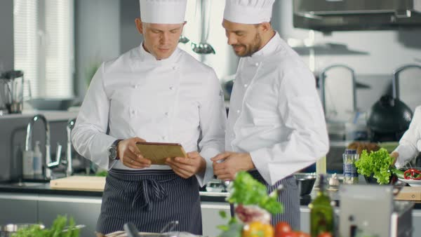 Two Chefs Exchange Ideas Watching on Tablet. They are Working in Big Restaurant Kitchen. Royalty-free stock video