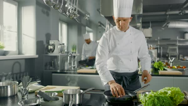 Chef Puts Fish on a Hot Pan in a Modern Kitchen. Royalty-free stock video