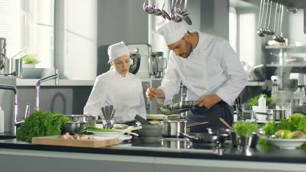 Chef and His Female Apprentice Prepare Special Dish in a Modern Restaurant's Kitchen. Royalty-free stock video