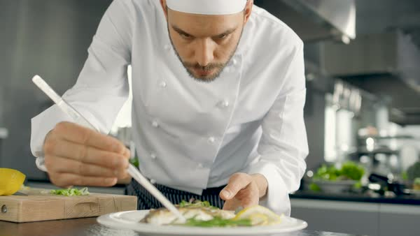 Chef Decorates His Special Fish Dish with Some Greens. He Works in a Modern Kitchen. Royalty-free stock video