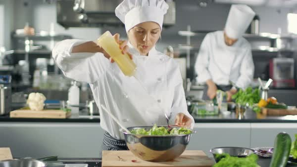 Female Cook Prepares Salad, adds Oil, in a Big Modern Kitchen. Royalty-free stock video