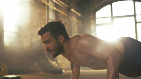 Muscular shirtless man covered in sweat does push-ups in a deserted factory remodeled into gym Royalty-free stock video