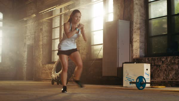 Fit athletic woman does footwork running drill in a deserted factory remodeled into gym Royalty-free stock video
