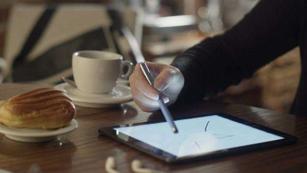 Woman drawing on tablet pc in coffee shop Royalty-free stock video
