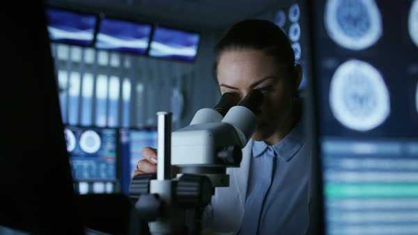 Medical research scientist looking under the microscope in the laboratory  stock footage
