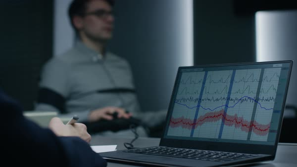 Computer shows physiological measures of a man undergoing lie detector /  polygraph test stock footage