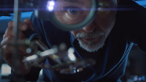 Electronics maintenance and repair engineer soldering motherboard,  microchip and circuit board, looking through magnifying glass  stock footage