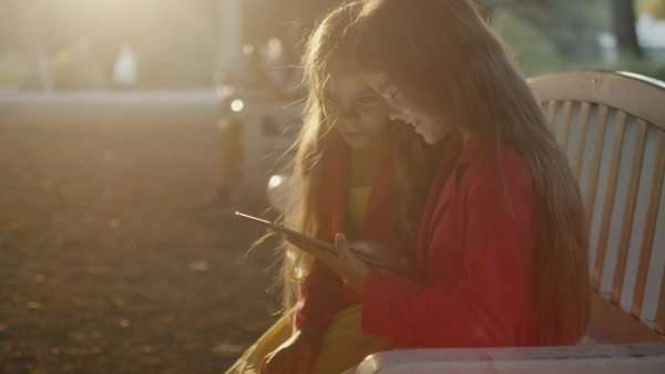 Twin girls are sitting at park and using tablet pc for entertainment at sunset Royalty-free stock video