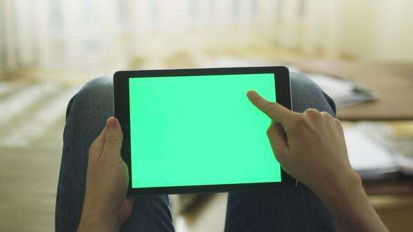 Man is laying on couch at home and using tablet with green screen in landscape mode on lap Royalty-free stock video