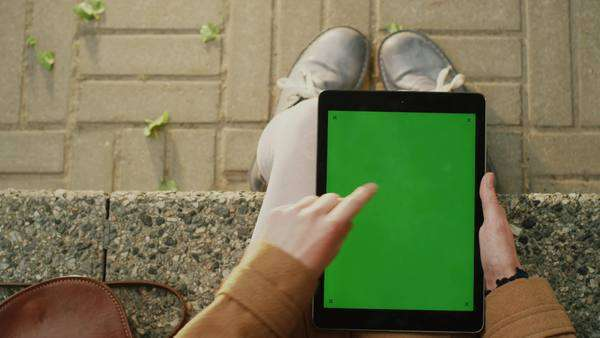 Girl is using tablet on lap outdoors at sunny day.  POV Royalty-free stock video