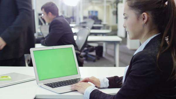 Female office worker using notebook with green screen. Royalty-free stock video