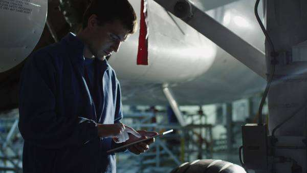 Aircraft maintenance mechanic uses tablet to inspect plane chassis in a hangar. Royalty-free stock video