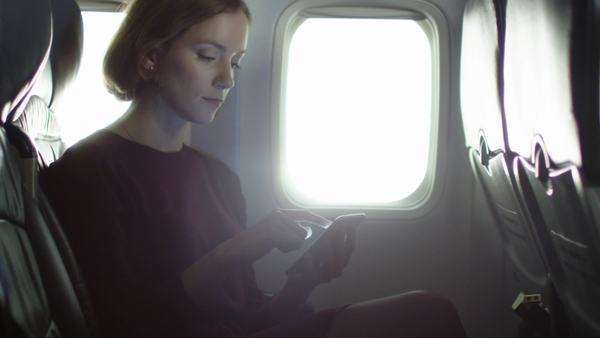 Young woman is using a smartphone inside an airplane next to a window. Royalty-free stock video