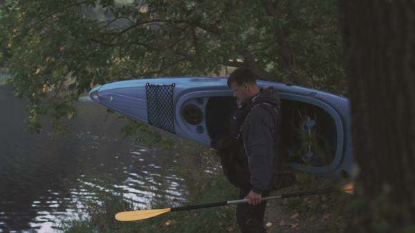 Man is carrying a blue kayak to the river shore and puts it on water. Royalty-free stock video