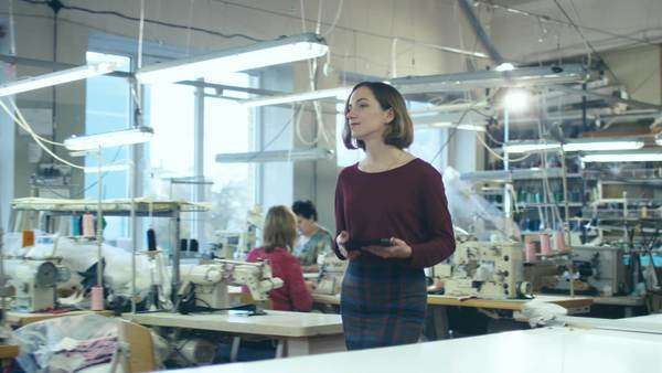 Young female with a tablet is walking through a clothing manufactory. Royalty-free stock video